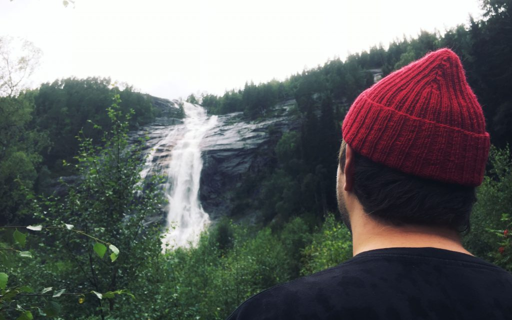 A man wearing a Red Cap, watching a waterfall.