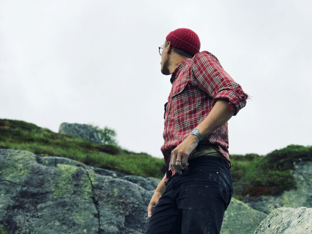 A man wearing a red handknitted cap looking across a mountain.
