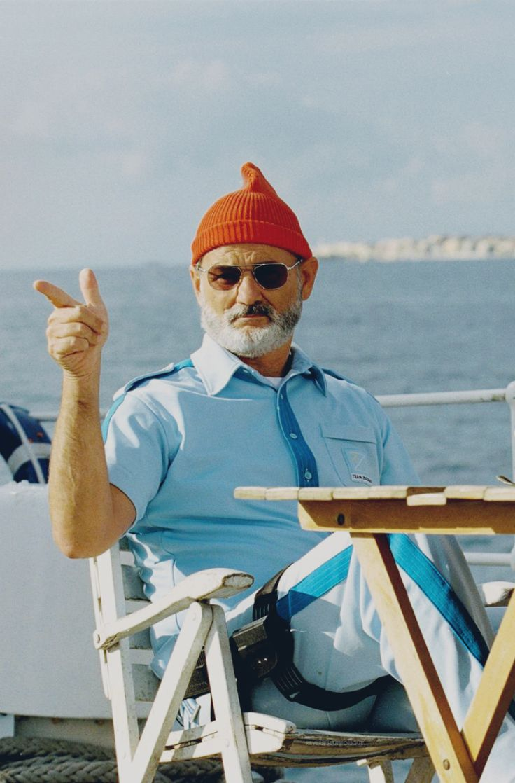 Steve Zissou points with his pointy red beanie