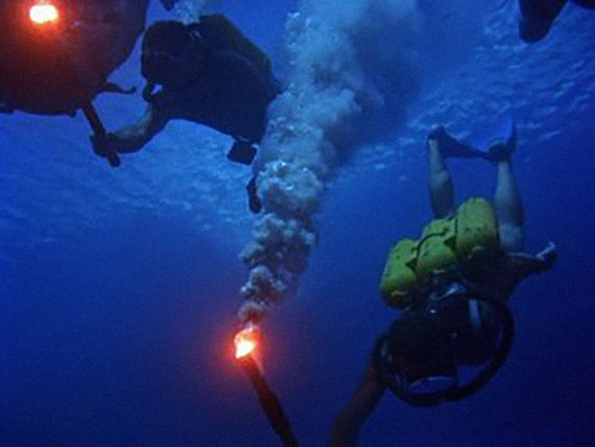 Jaques Cousteau diving with flares.
